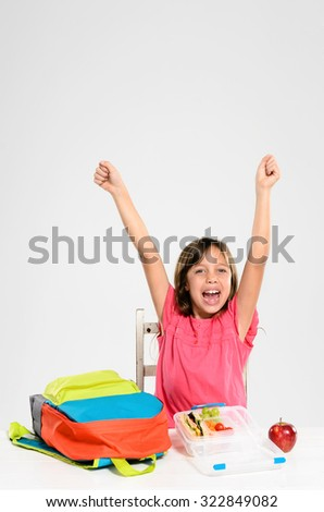 Happy smiling school girl with her arms up loving school and celebrating her healthy packed lunch - stock photo