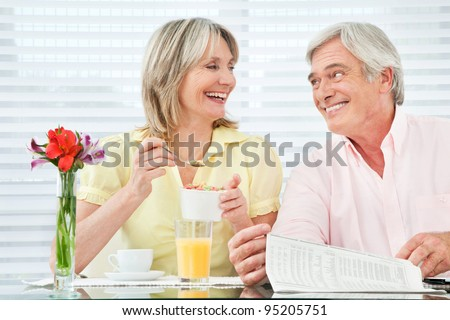 Happy smiling senior couple eating breakfast at home - stock photo