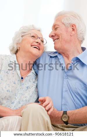 Happy smiling senior couple laughing together at home - stock photo