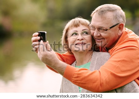 Happy smiling senior couple taking picture of themselves with smartphone outdoor - stock photo