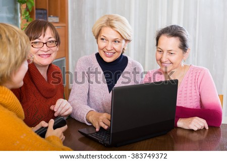 Happy smiling senior female friends working with notebook using wifi