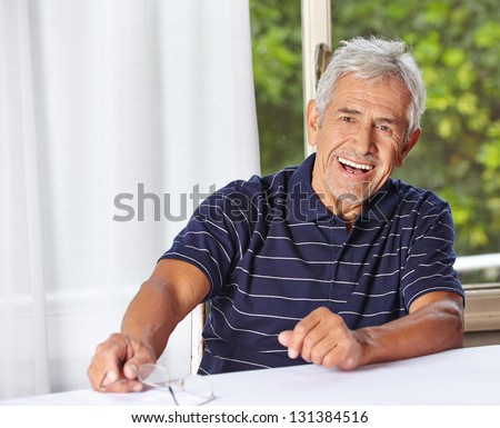 Happy smiling senior man sitting with reading glasses at a table - stock photo