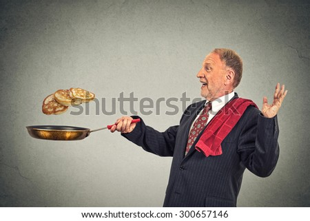 Happy smiling senior man tossing pancakes on frying pan isolated on gray wall background. Positive face expression emotion, Kitchen fun concept