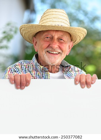 Happy smiling senior man with a straw hat holds a blank board - stock photo