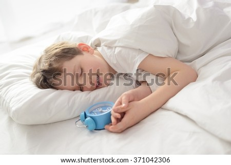 Happy smiling sleeping little boy with alarm clock near his head. Sleeping boy. Sleeping child - stock photo