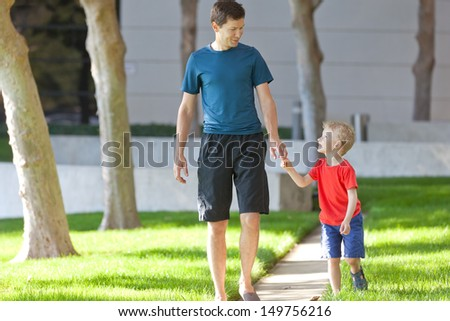 happy smiling son and his handsome father having a leisure nature walk together - stock photo