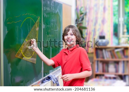 Happy smiling student boy enjoying his first day back to school at a mathematics lesson standing at a chalk board drawing for geometry study with triangle ruler on a big class room with window - stock photo