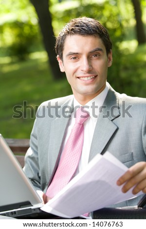 Happy smiling successful businessman working with laptop outdoors