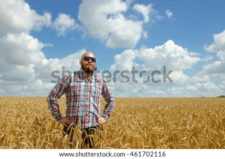 Happy smiling successful caucasian thirty years old farmer standing proud in front of his wheat fields.