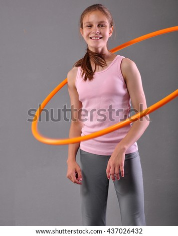 Happy smiling teenage sportive girl is doing exercises with hula-hoop to develop muscle on grey background. Having fun playing game hula-hoop. Sport healthy lifestyle concept. - stock photo