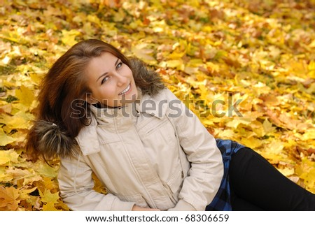 Happy smiling teenager girl lying in autumn park - stock photo