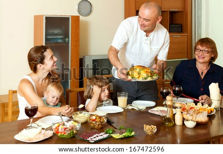Happy smiling three generations family eating chicken over  table at home interior - stock photo