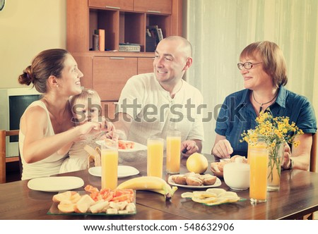 Happy smiling three generations family eating fresh friuts and vegitables at home
