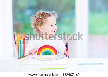 Happy smiling toddler girl drawing a rainbow next to a big window  - stock photo