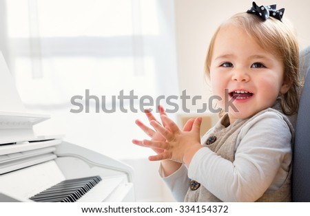 Happy smiling toddler girl excited to play the piano - stock photo