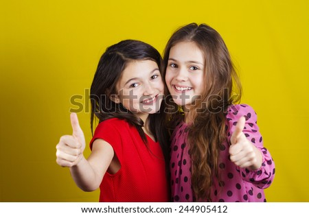 Happy smiling two little girls, schoolgirls with thumb up isolated over yellow background. - stock photo