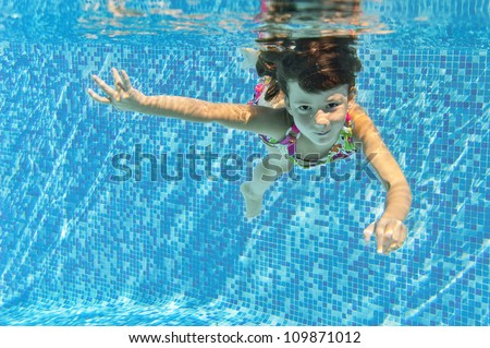 Happy smiling underwater child in swimming pool, beautiful healthy girl swims and having fun. Kids sport on family summer vacation. Active holiday
