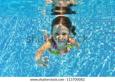 Happy smiling underwater child in swimming pool, beautiful healthy girl swims and having fun. Kids sport on family summer vacation. Active holiday - stock photo