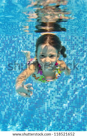 Happy smiling underwater child in swimming pool, beautiful healthy girl swims and having fun. Kids sport on family summer vacation. Active holiday. Vertical image - stock photo