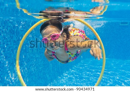 Happy smiling underwater child in swimming pool. Little girl swims. Kids sport - stock photo
