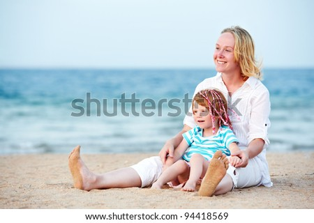 Happy smiling Woman and child playing at red sea beach during sunset - stock photo