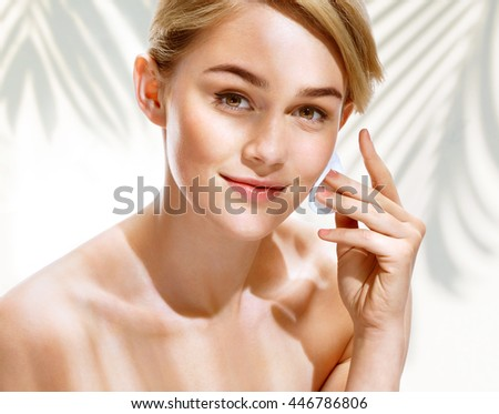 Happy smiling woman cleaning skin by cotton pad. Photo of attractive blonde girl in sunny summer day. Youth and skin care concept