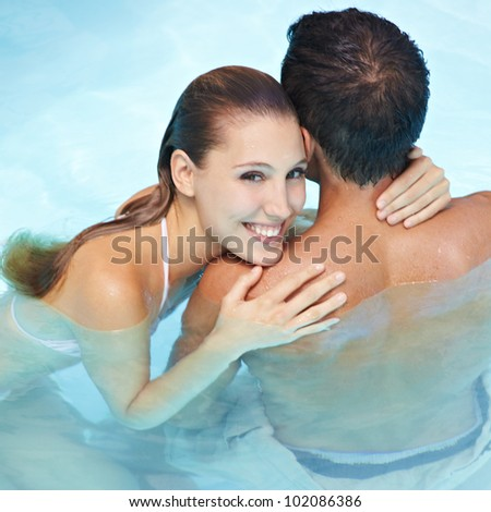 Happy smiling woman embracing attractive man in blue water - stock photo