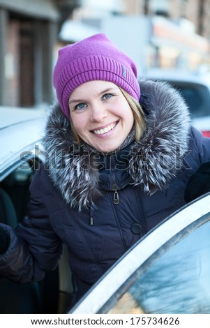 Happy smiling woman get in the car - stock photo