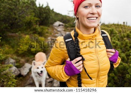 Happy smiling woman hiking in mountains with akita dog, Karkonosze Mountain Range. Young female hiker smiling, sport and trekking in autumn nature. - stock photo