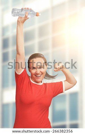 Happy smiling woman holding bottle in hand over her head and shout