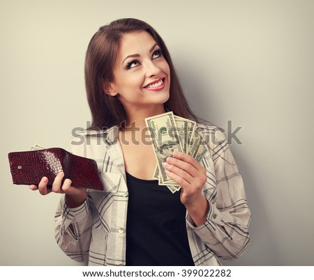 Happy smiling woman holding wallet and dollars and thinking how to spent its. Toned portrait - stock photo