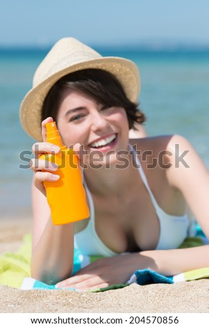 Happy smiling woman in a trendy straw hat lying on a towel on a tropical beach with a bottle of suntan spray in her hand, close up of her head and shoulders as she faces the camera - stock photo