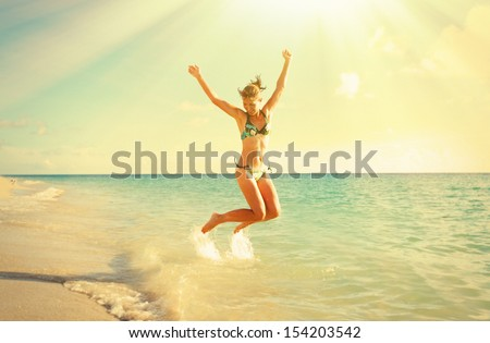 Happy smiling woman in bikini jumping in  sea