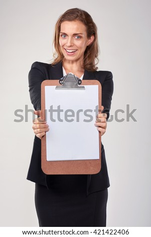 Happy smiling woman in business suit showing blank clipboard with copy space - stock photo