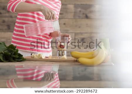 Happy smiling woman in kitchen preparing fresh fruit cocktail - stock photo