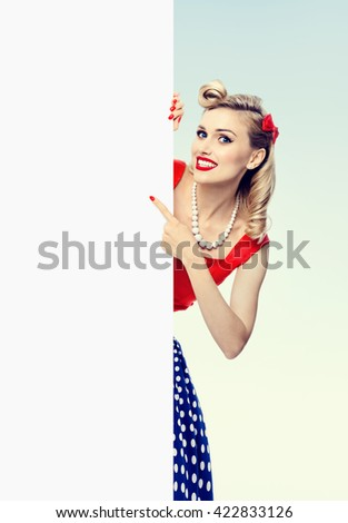 happy smiling woman in pin-up style dress, showing blank signboard with copyspace. Caucasian blond model posing in retro fashion and vintage concept studio shoot. - stock photo