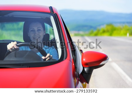 Happy smiling woman in red car. Driving.