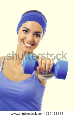 Happy smiling woman in violet sportswear, doing fitness exercise with dumbbell. Young sporty dark-haired model at studio shot. Health, beauty and fitness concept. - stock photo