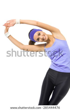 Happy smiling woman in violet sportswear doing stretching exercise or youga moves, isolated against white background. Young sporty dark-haired model at studio shot. Health, beauty and fitness concept.