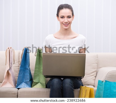 Happy, smiling woman is using laptop while sitting on the couch with shopping bags. - stock photo