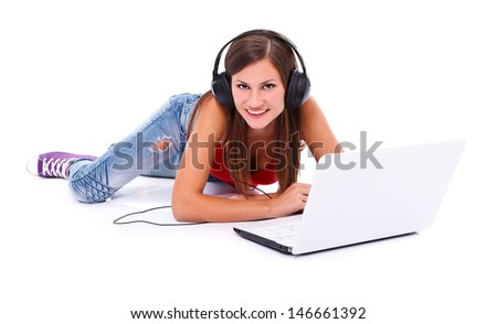 Happy smiling woman lying on belly with headphones behind a laptop. Isolated on white.