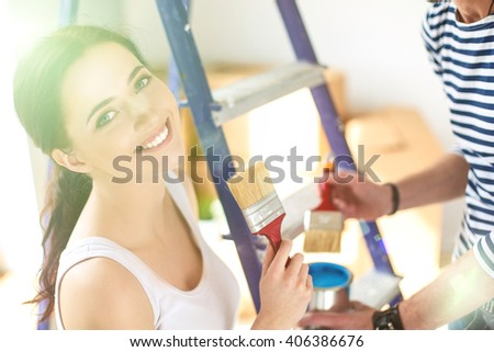 Happy smiling woman painting interior wall of new house - stock photo