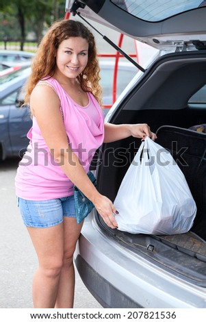 Happy smiling woman putting shopping bags into the car trunk  - stock photo