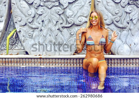 Happy smiling woman relaxing at the pool - stock photo