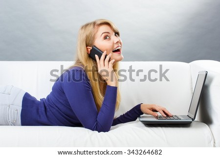 Happy smiling woman talking on mobile phone and using laptop lying on sofa, typing on computer keyboard, surfing internet, modern technology - stock photo