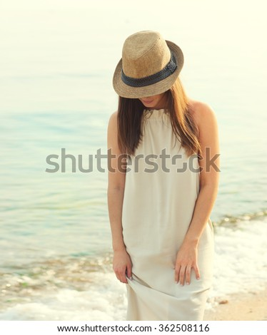 Happy smiling woman walking on a sea beach dressed in white dress and hat covering face, relaxing and enjoy fresh air, outdoor portrait. - stock photo