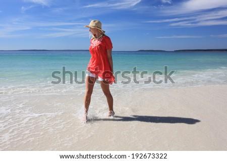 Happy smiling woman wearing a sun hat splashing feet while walking along the beach.   Some motion in splashing water and feet. - stock photo
