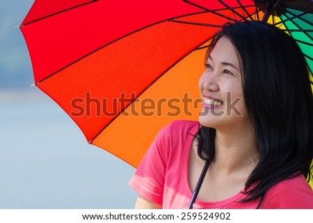 Happy smiling woman with an umbrella. On a clear day The backdrop is a mountain in the dam. - stock photo