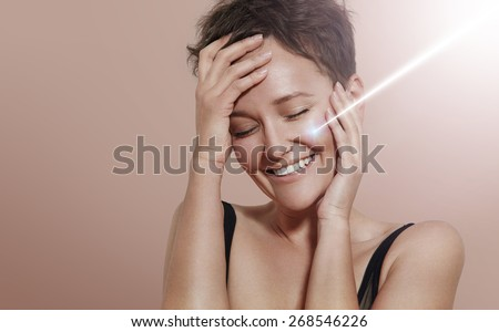 happy smiling woman with ray of laser on her ideal skin