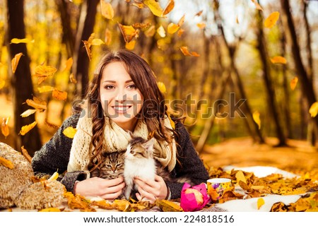 happy smiling woman with two cats under falling autumn leafs